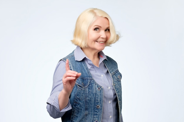 上向きとカメラ目線の陽気な年配のブロンドの女性