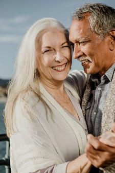 Веселая пара старших танцует на пирсе санта-моники