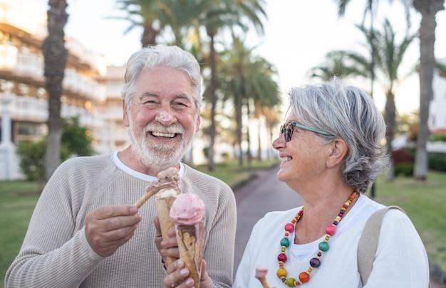 公園でアイスクリームコーンを食べる陽気な年配のカップル。彼女の妻は、アイスクリームで覆われた夫の鼻を面白がっているように見えます。うれしそうな高齢者のライフスタイルのコンセプト。背景の海とヤシの木