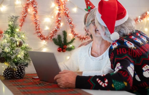 Веселая старшая пара обнимается и целуется в рождественской сладкой шляпе санта-клауса, празднующей рождество