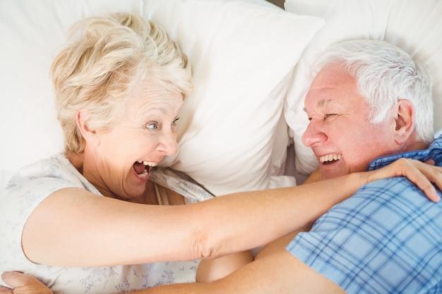 Cheerful senior couple enjoying on bed