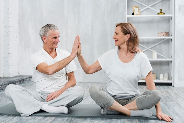 Cheerful senior couple giving high five while exercising together on mat
