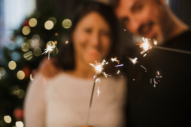 Cheerful senior couple holding fireworks