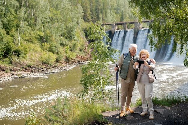 Веселая старшая пара в спортивной одежде делает селфи на фоне водопадов, стоя на берегу реки в лесу