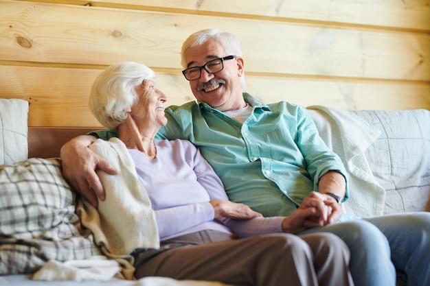 Веселая старшая пара в повседневной одежде обсуждает новости или планы, отдыхая на диване в своем загородном доме