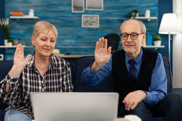 Cheerful senior couple in living room waving at webcam