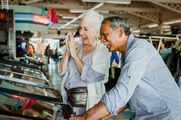 アーケードでゲームをしている陽気な年配のカップル