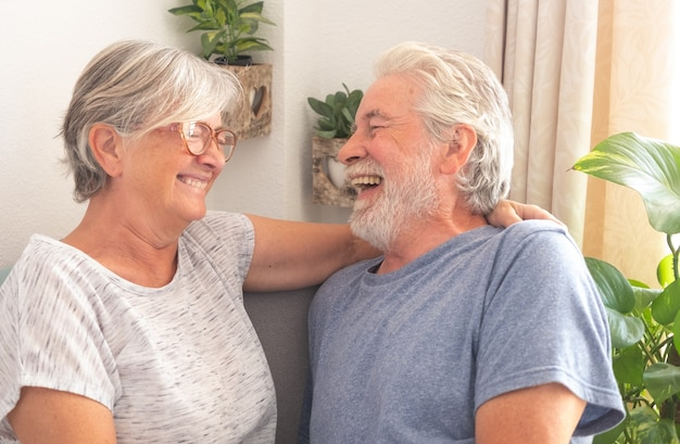쾌활한 노인 부부는 집에서 거실에 앉아 근심 걱정 없이 웃고 있다