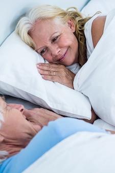 ベッドで寝ている陽気な年配のカップル
