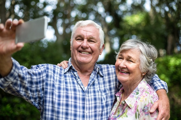 Cheerful senior couple taking selfie in back yard