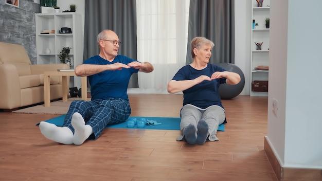 一緒にヨガマットに座ってトレーニングする陽気な老夫婦。高齢者の健康的でアクティブなライフスタイルの運動と自宅でのトレーニング、高齢者のトレーニングとフィットネス
