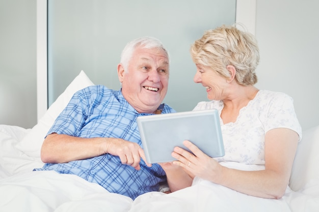 Cheerful senior couple using digital table on bed