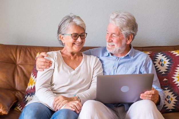 Веселая пара старших с помощью ноутбука, сидя на диване и улыбаясь. пожилая пара счастлива расслабляющий во время серфинга на ноутбуке, сидя в гостиной. старая пара смотрит медиа-контент с помощью ноутбука