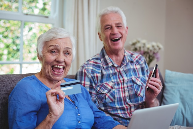 Cheerful senior couple with credit card and technology