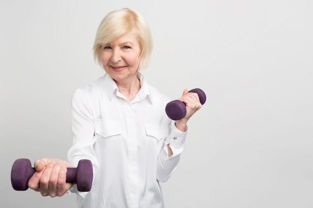 Cheerful senior lady exercising with light weights. she likes to do that because after exersices she feels much better.
