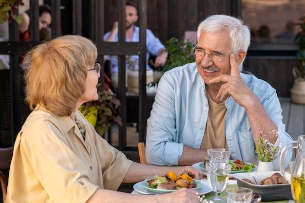 Веселый старший мужчина и его жена обсуждают что-то за ужином на открытом воздухе