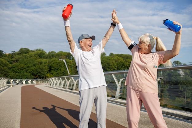 Веселый старший мужчина и женщина поднимают бутылки и берутся за руки на пешеходном мосту