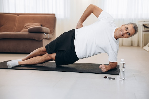 Жизнерадостный старший мужчина делает упражнения боковой планки на коврике для йоги. как сохранить здоровье на карантине. здоровый образ жизни. спортивная (ый) человек тренировки и глядя на камеру. современная гостиная на фоне.