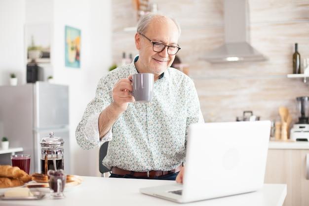 朝食とコーヒーを楽しみながらキッチンでビデオ会議中に陽気な年配の男性。インターネットオンラインチャット技術を使用している高齢者がビデオ通話接続を行うビデオウェブカメラが来ました