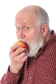 Cheerful senior man eating the apple, isolated