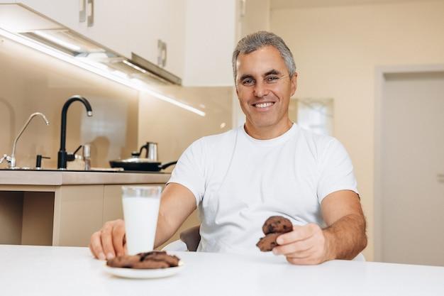 Веселый пожилой мужчина в белой футболке имеет стакан молочного и шоколадного печенья