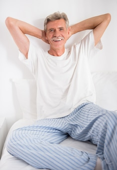Cheerful senior man is sitting in bed and looking at camera.