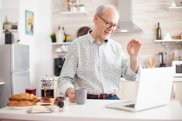 朝食とコーヒーを楽しみながら、キッチンからオンラインビデオ通話で陽気な年配の男性。インターネットオンラインチャット技術を使用している高齢者ビデオウェブカメラがビデオ通話接続カムを作成している