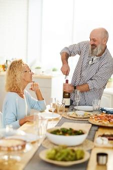 Веселый старший мужчина открывает бутылку вина