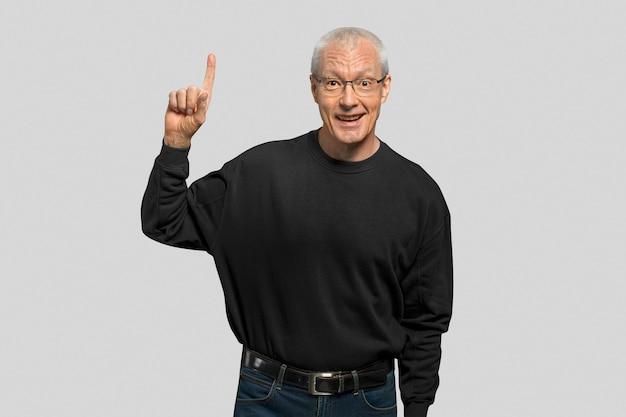 Uomo anziano allegro che punta il dito in alto nel ritratto dell'aria