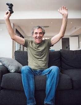 Cheerful senior man sitting on sofa raising her arms holding joystick at home