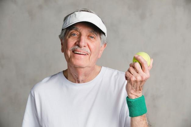 Веселый старший мужчина с теннисным мячом