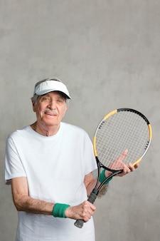 Веселый старший мужчина с теннисной ракеткой