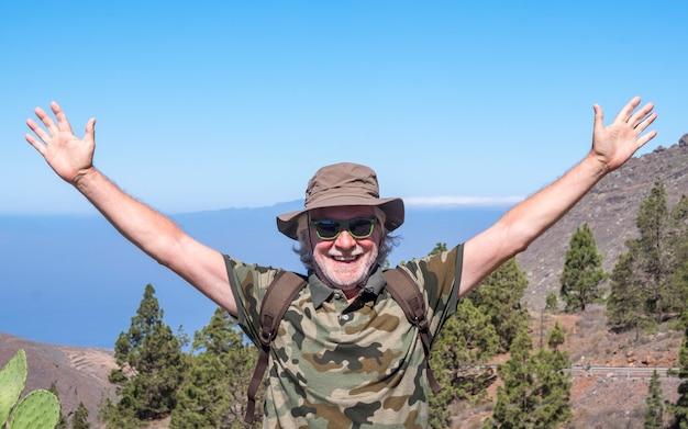 테네리페의 산 풍경을 여행하며 미소를 지으며 자유를 즐기는 쾌활한 노인 - 바다 너머 지평선 - 활동적인 은퇴한 노인과 재미있는 개념
