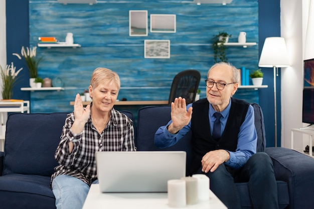 Cheerful senior man and woman waving during online call with family