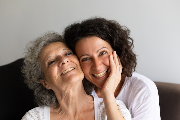 Cheerful senior mother and adult daughter posing at home