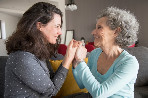 Cheerful senior mother and her daughter holding hands