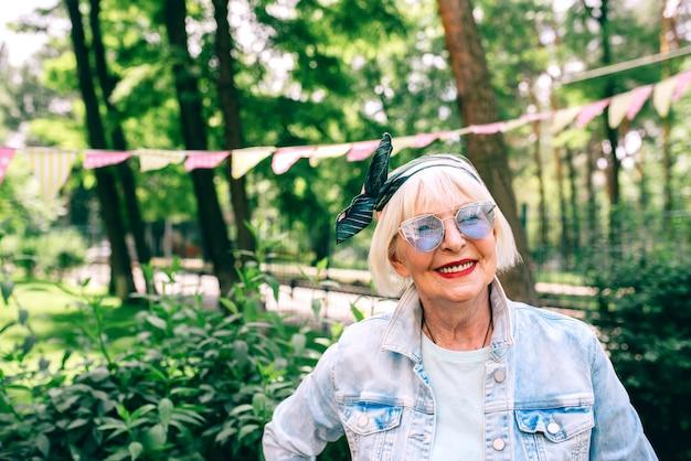 Веселая старшая старая стильная женщина с седыми волосами и в синих очках и джинсовом мастере праздника
