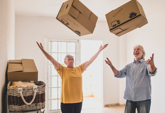 Веселые пожилые люди в пустой комнате, играющие, как дети в переезде, счастливы для нового начала, как пенсионеры с движущимися коробками на полу