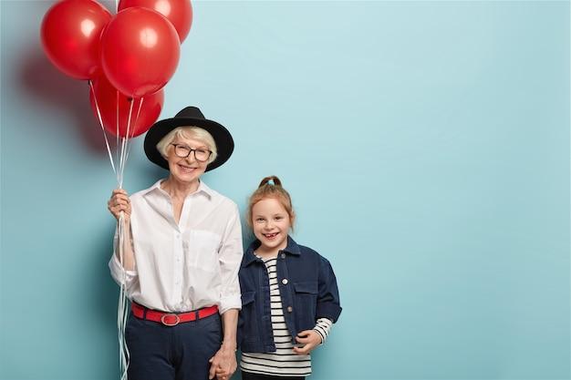 陽気な年配の女性と小さな孫娘が手をつないで、前向きな姿勢、嬉しい表情、スタイリッシュな服を着て、こどもの日を祝うお祭りイベントに参加します。二世代