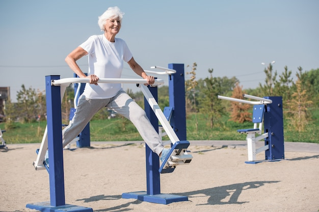 Cheerful senior woman exercising outdoors
