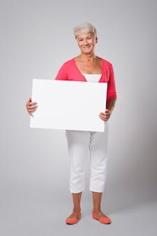Веселая старшая женщина, держащая пустую доску