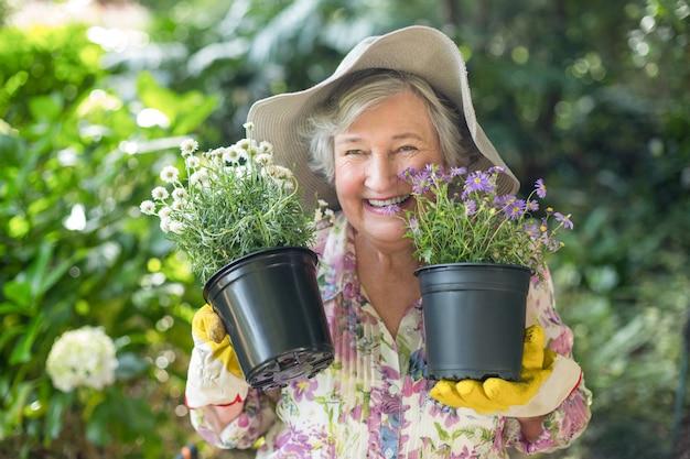 鉢植えの植物を保持している陽気な年配の女性