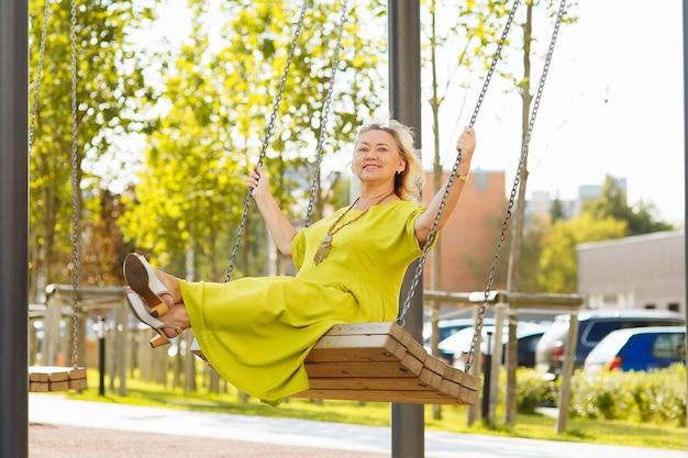 公園でブランコに乗って陽気な年配の女性