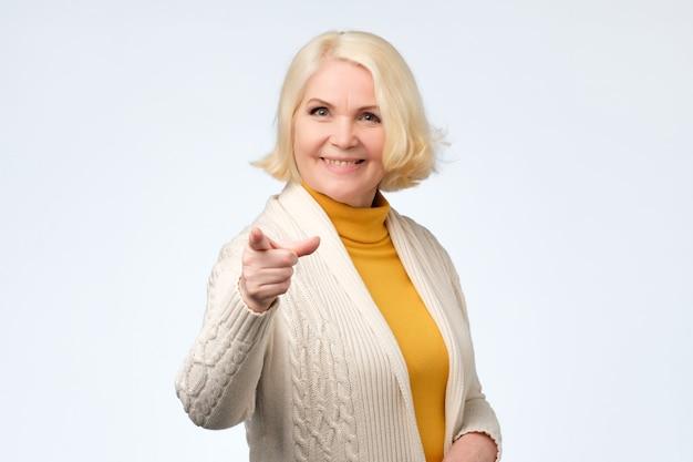 カメラで陽気な年配の女性人差し指