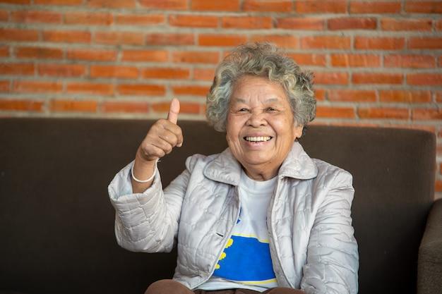 집의 아늑한 거실에 있는 소파에 앉아 있는 쾌활한 노년의 여성, 웃고 있는 노부인의 초상화.