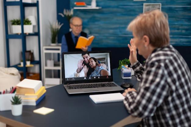 Жизнерадостная пожилая женщина машет перед вебкамерой во время онлайн-разговора с родственниками счастливая бабушка говорит, что он ...