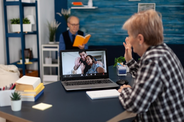 Cheerful senior woman waving at webcam during online call with relatives happy grandmother saying he...