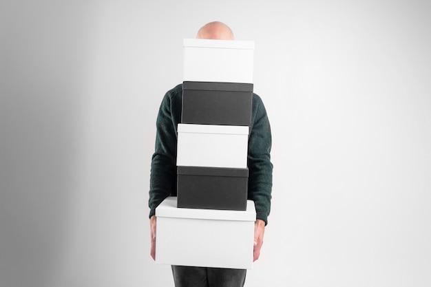 우아한 옷을 입고 쾌활한 심각한 남자는 검은 색과 흰색 상자를 보유하고