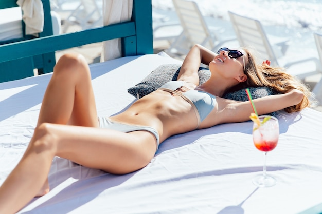 Cheerful sexy woman skinny body in sunglasses and swimsuit, tanning while resting