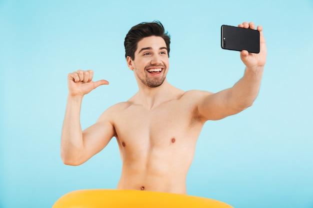 孤立して立っている陽気な上半身裸の男、膨脹可能なリングで自分撮りを取る